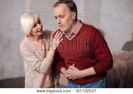 Are you ok. Pretty aged woman standing near her senior husband with terrible stomachache and supporting him.