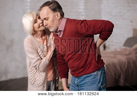 It will be gone. Portrait of elderly man leaning while having strong backache and his wife supporting him.
