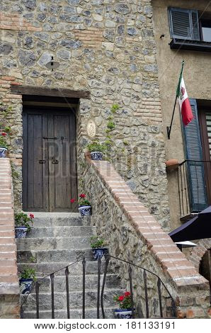 VAL'QUIRICO, TLAXCALA, MEXICO-MARCH 25, 2017: Facade of a building with stone walls and an ancient door at a street in Val'Quirico, a new town near to Tlaxcala, Mexico