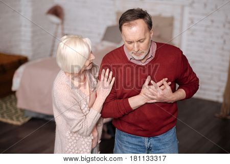 Im not good. Portrait of elderly man standing and touching his heart area while his loving wife supporting him during this time.