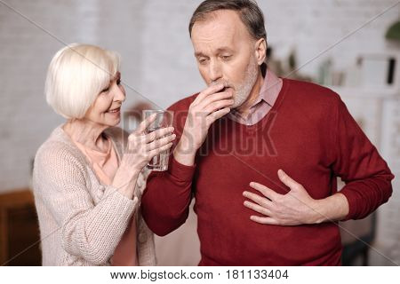 Drink water. Aged man with bronchitis standing and coughing while his wife offering him glass of water.
