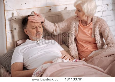 You got cold. Elderly woman sitting on bed near her ill husband and feeling his body temperature by touching his forehead.