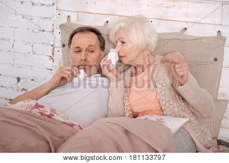 How could we. Very sick elderly couple lying on bed covered with blankets and blowing their noses.