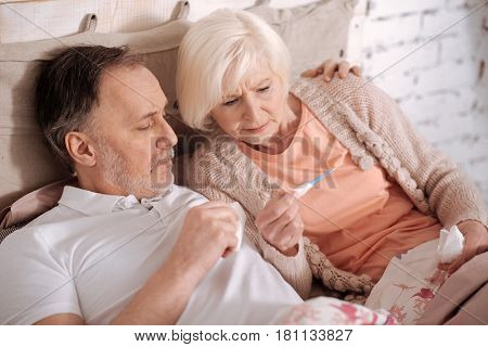 We have fever. Top view of elderly couple lying on bed and checking time on thermometer.
