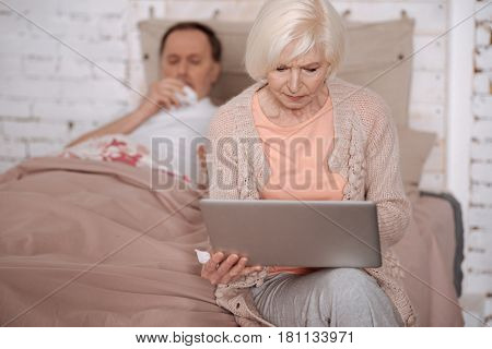 Looking for doctor. Elderly lady sitting on bed in front of her ill husband and using her modern laptop.
