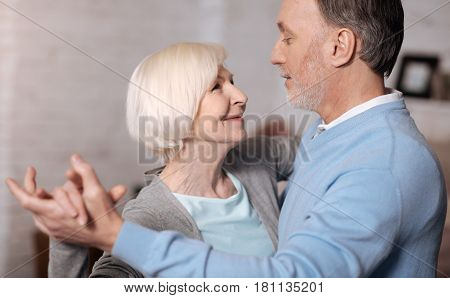 Long time together. Close-up portrait of happy senior man and woman standing and looking at each other while dancing.