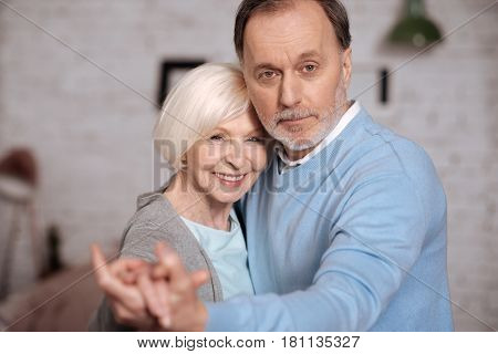 We love. Close-up portrait of pretty smiling elderly woman standing near her husband and holding hands.