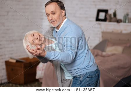 Celebrating anniversary. Elderly man leaning her senior wife while dancing with her at home.