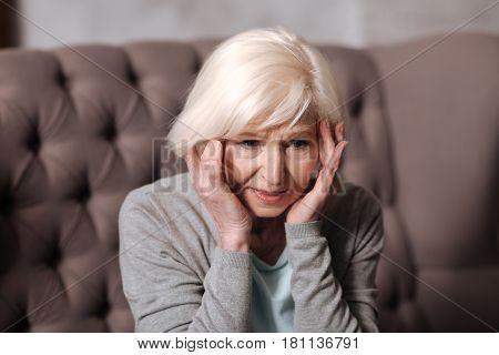 So uncomfortable. Close up portrait of pretty senior woman feeling bad because of headache.