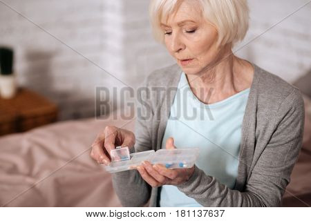 Need medical support. Close up portrait of sad aged lady holding transparent case while going to take drugs.
