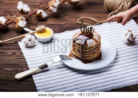 American pancakes on a plate with mint, caramel, syrup, love sign, honey and sugar powder. Also, a child hand pointing on pancakes. With the cotton branch on a back.