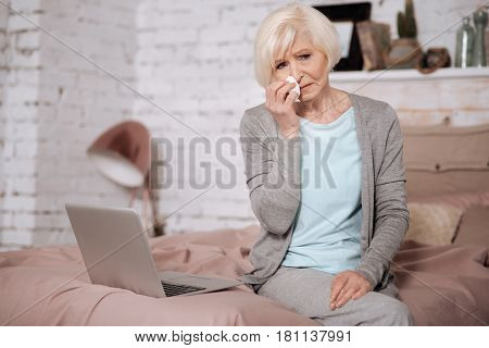 Very bad news. Portrait of sad senior woman sitting on bed and wiping nose with napkin.