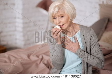 Feeling discomfort. Pretty aged woman sitting on bed and touching her chest while coughing