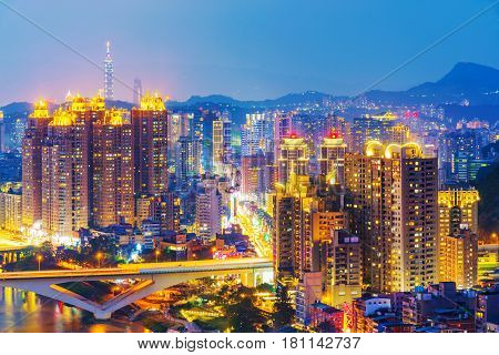 Night view of New Taipei riverside city buildings in Xindian