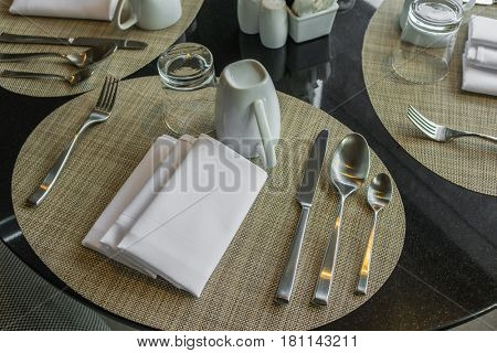 Table appointments- fork,knife,spoon, silk napkin on bamboo mat