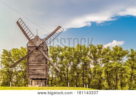 Large Russian wooden windmill on a background of green trees. Summer landscape.