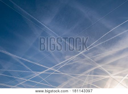 Intricate pattern of contrails against a blue sky