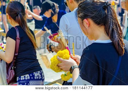 BANGKOK THAILAND - FEBRUARY 07: Girl praying at Erawan buddhist shrine with incense sticks in her hands on February 07 2017 in Bangkok