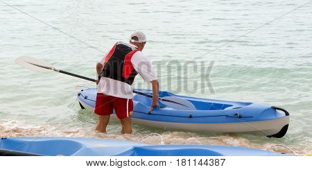 Man with blue canoe on tropical sea