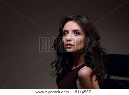 Sexy Young Makeup Model With Effect Brow And Curly Hairstyle Posing On Dark Shadow Background And Lo