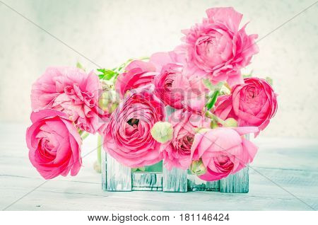 The soft pink Ranunculus flowers in white wooden box. Horizontal studio shot. Background space for text. Natural vintage mock up
