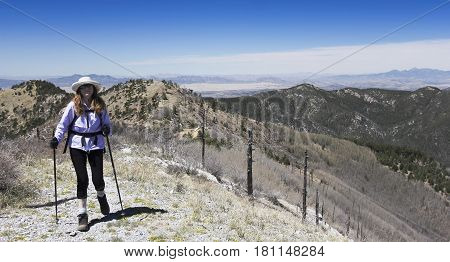 A Woman Hiker Makes Her Way to the Summit of a Mountain Peak