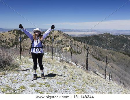 A Woman Hiker Celebrates Reaching the Summit of a Mountain Peak