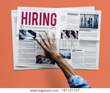 Hand reaching to grab newspaper for hiring job announcement