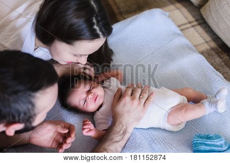 Parents with Newborn Baby Boy. Young parents look at a sleeping baby. View from above. Father's hand caressing a child