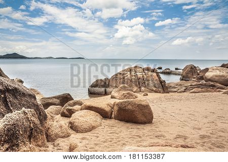 Sandy tropical beach with big round stones and blue sky