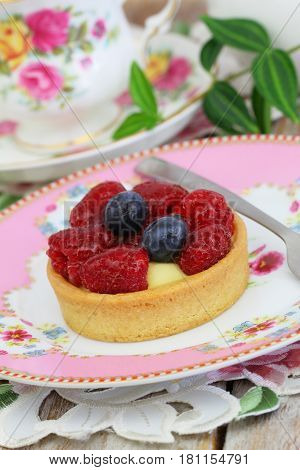 Delicious crunchy cream cake with fresh raspberries and blueberries