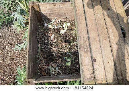 wooden compost bin in a family garden