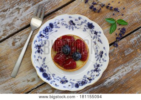 Crunchy tartelette with fresh fruit on vintage plate on rustic wood
