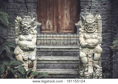 Ancient Asian demons deities at the enter to the old temple with old wooden door and stone steps in vintage style
