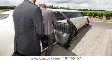 driver holds the open door of the limousine so that the gentleman goes inside