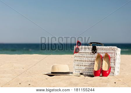Summer vacation at sea. White wicker suitcase and women's accessories and shoes on the beach. Selective focus.