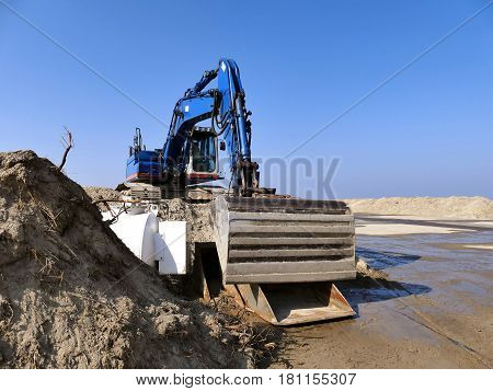 Blue Excavator On Pile Of Sand On Construction Site