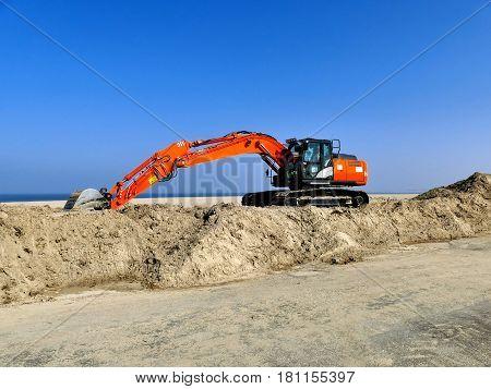 Orange Excavator On Pile Of Sand Near Beach