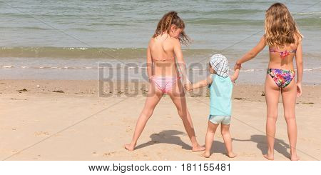 Back view of a happy children on beach