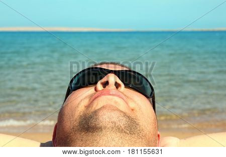 man face close-up relaxing on beach