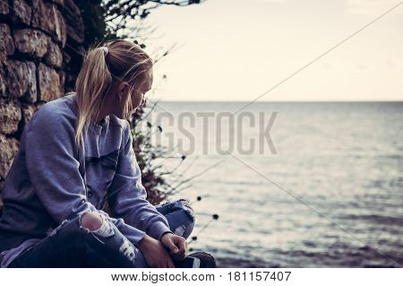 Thoughtful lonely young woman tourist with closed eyes thinking during her travel sitting on seashore in retro vintage style