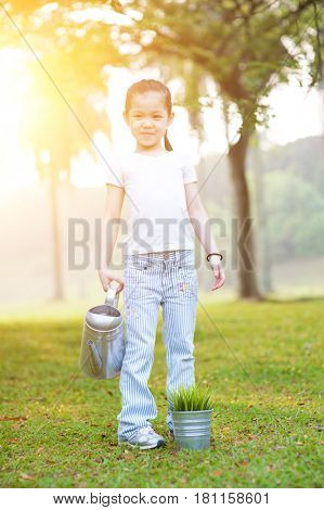 Portrait of cute Asian kid watering plant outdoors. Little girl having fun at nature park. Morning sun flare background.