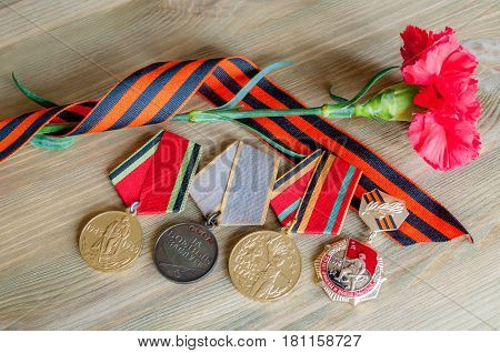 VELIKY NOVGOROD,RUSSIA-CIRCA APRIL, 2017.9 May Victory day card with medals of Great patriotic war, red carnations and George ribbon as symbol of 9 May on the wooden background. 9 May concept