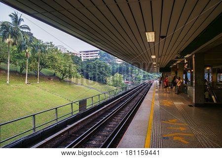 Singapore. October 2010. Passengers waiting on the platform Ang Mo Kio above-ground MRT Station.