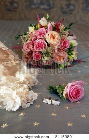Beautiful wedding bouquet from pink roses and groom cufflinks