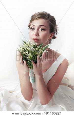 The beautiful bride with bouquet in studio