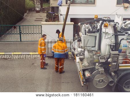PARIS FRANCE - DEB 10 2017: Workers using sewerage truck and large pipe working on the clogged street rain water drain repairing and maintenance