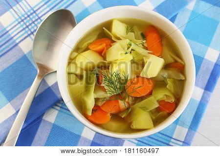 Cabbage soup in bowl garnished with fresh dill on checkered cloth