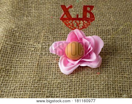 one egg in the shape of a flower to the Easter holiday to paint with pink petals on a wooden table and the letters X V written Christ is Risen