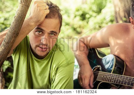 Candid young man with sincere look singing with guitar during outdoor camping party among foliage
